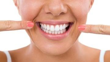 A woman points to her teeth | bridgeton mo cosmetic dentistry