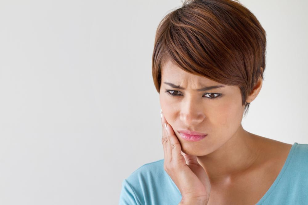 woman holding jaw in pain | TMJ Dentist Bridgeton MO