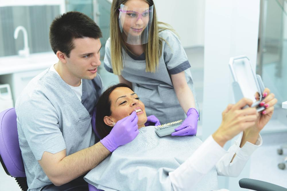 Woman holding up mirror during dental exam to see her new veneers in Bridgeton MO