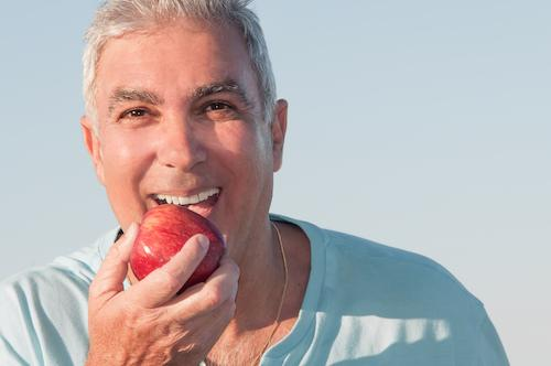 Man eating apple with dentures and partials in Bridgeton, MO