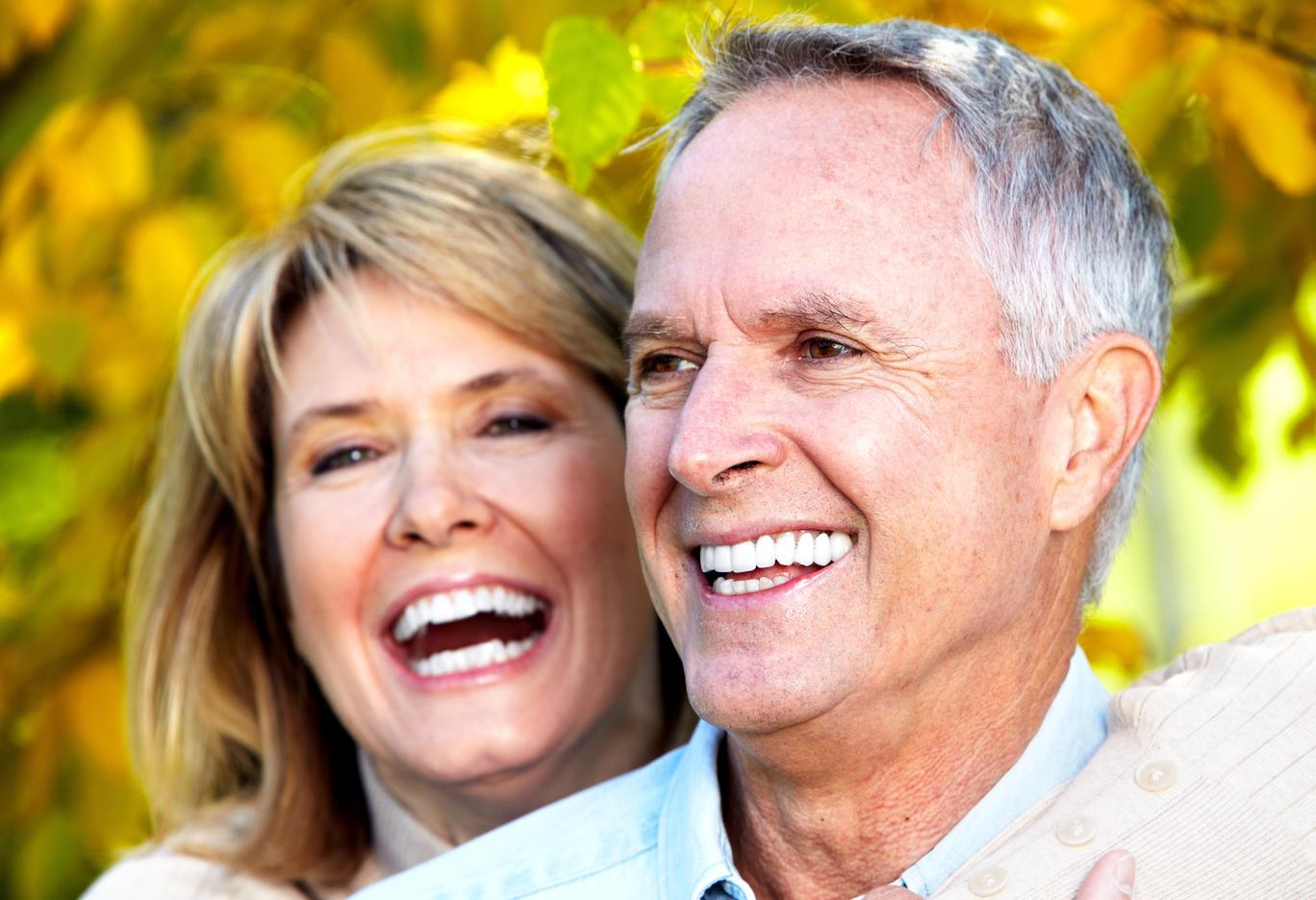 An older couple smiles outdoors | dentures and partials in Bridgeton, MO