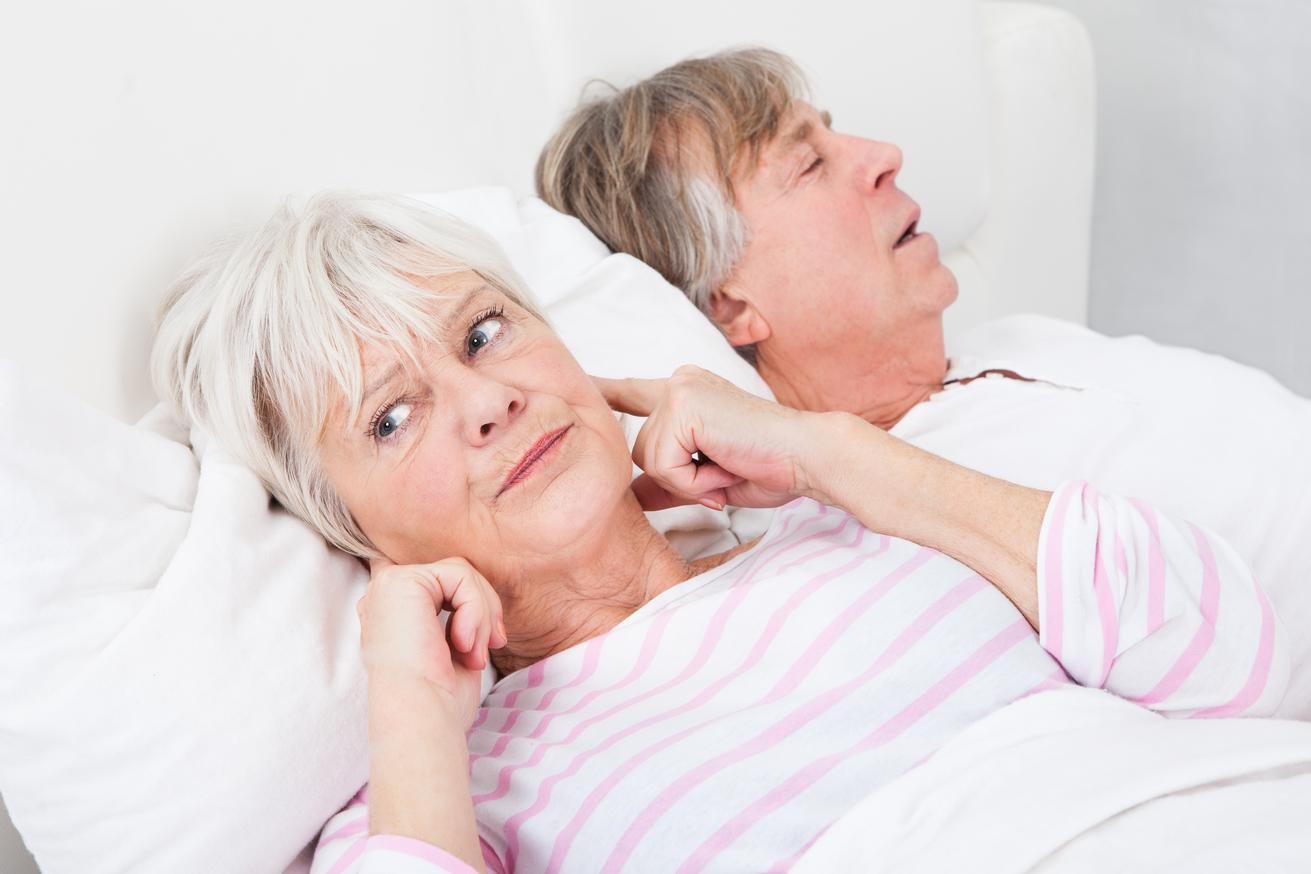 a woman plugs her ears as she lays next to her husband | sleep apnea treatment bridgeton mo