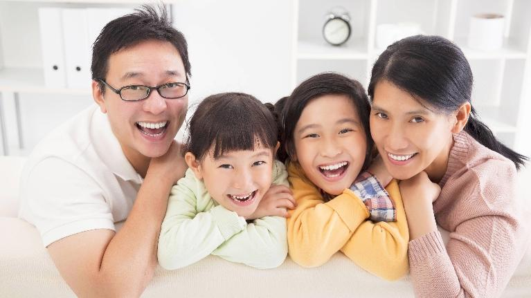 A family smiles in a white room | Dentist Bridgeton MO