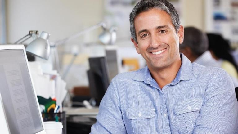 Man sitting in an office smiling | Dental Implants Bridgeton MO