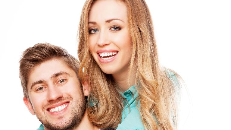A couple smiles over a white backdrop | Bionic Teeth in Bridgeton MO