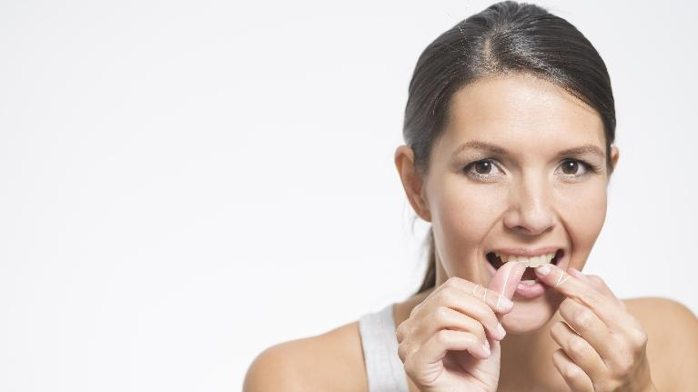 A woman flosses her teeth | Dental Implants Bridgeton MO