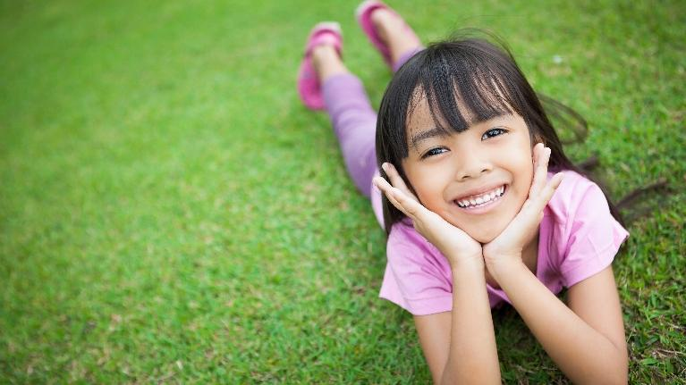 A child smiles in a field | pediatric dentist bridgeton MO