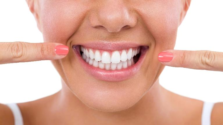 A woman points to her smile | Cosmetic Dentistry Bridgeton MO