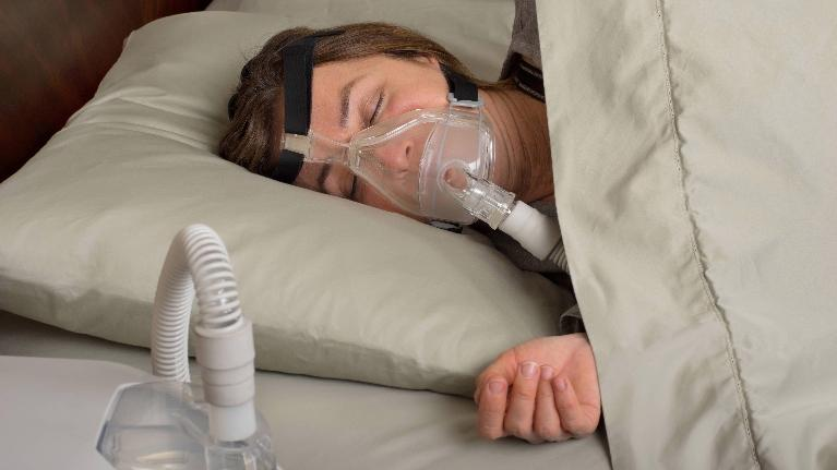 A woman sleeps with her CPAP machine | Dentist Bridgeton MO