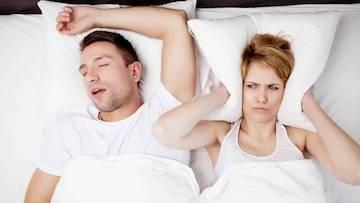 A woman covers her ears with her pillow next to her sleeping partner | Sleep apnea bridgeton