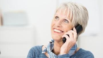 A woman smiles as she talks on the phone | Dental Implants Bridgeton, MO