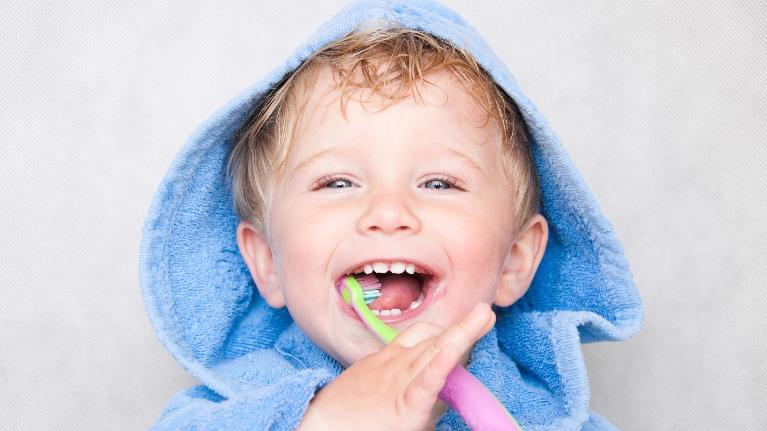 A child smiles while brushing his teeth | Bridgeton MO Pediatric Dentist
