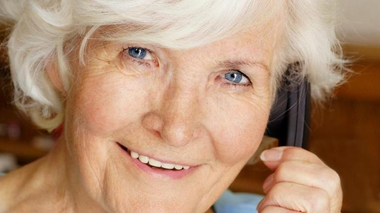 a woman smiles on the phone | dentures Hazelwood mo