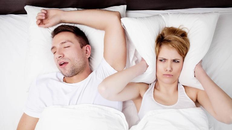 A woman covers her ear with her pillow due to her partner's sleeping | Bridgeton Mo Dentist