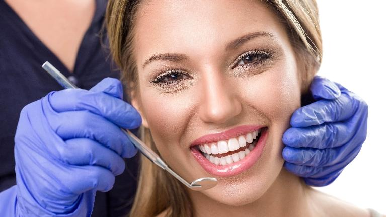 a woman smiles in the dental chair | dental implants bridgeton
