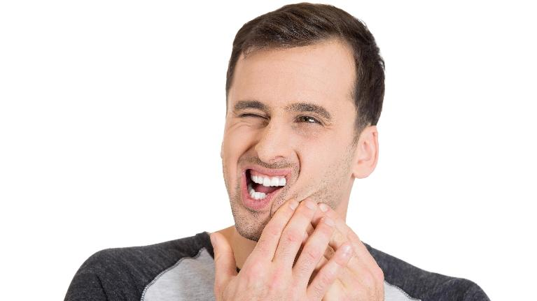 A man holds his jaw | Bruxism Treatment Bridgeton MO